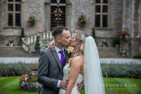 Bride and Groom kiss in front of Clearwell castle